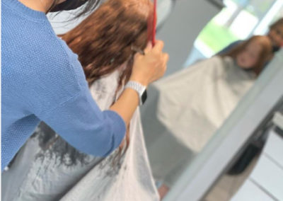 Stylist running comb through clients red hair to remove tangles